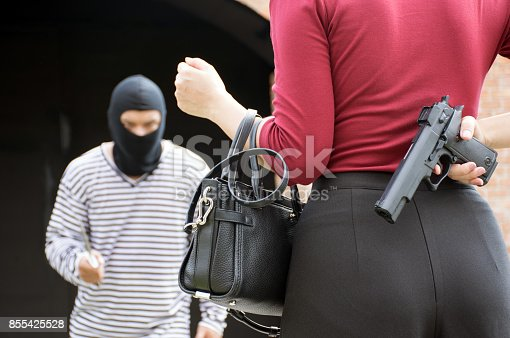 istock Male robber standing and looking at young woman and young woman hide gun in his back 855425528