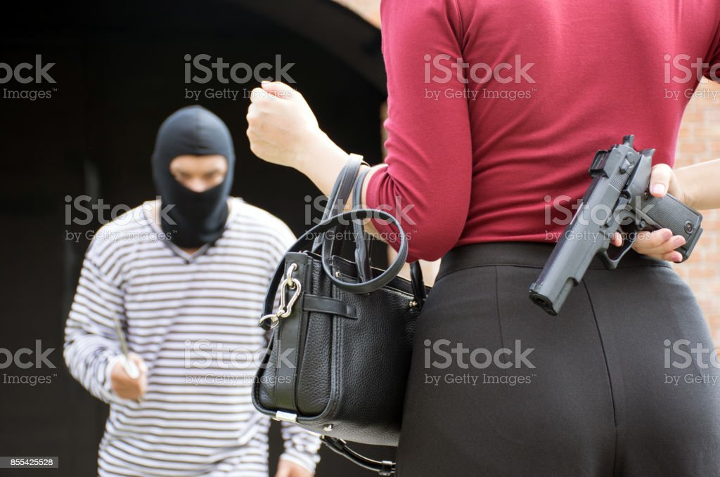 Male robber standing and looking at young woman and young woman hide gun in his back stock photo
