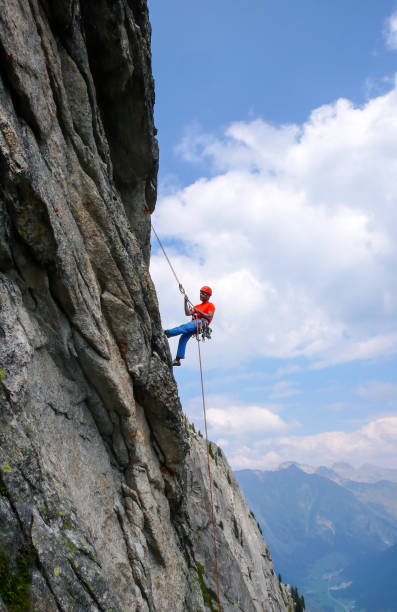 male rock climber abseiling off a steep rock climbing route in the swiss alps after a hard climb - брегалья стоковые фото и изображения