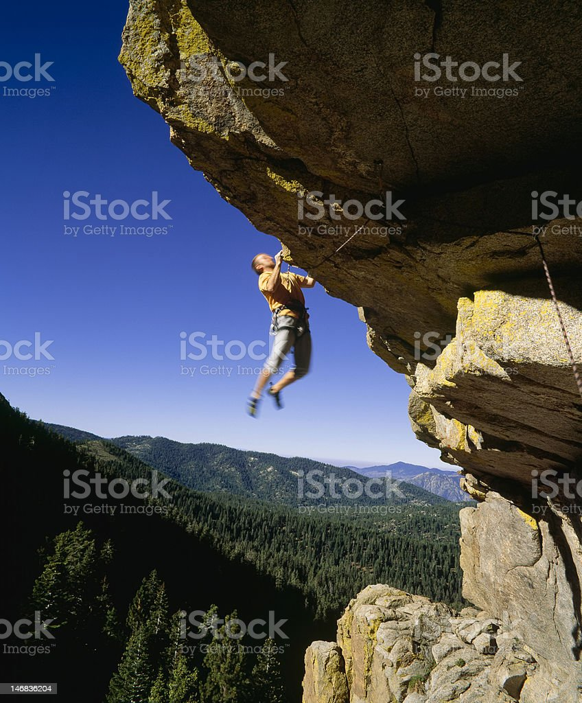 Male rock climber clinging to an overhang. stock photo