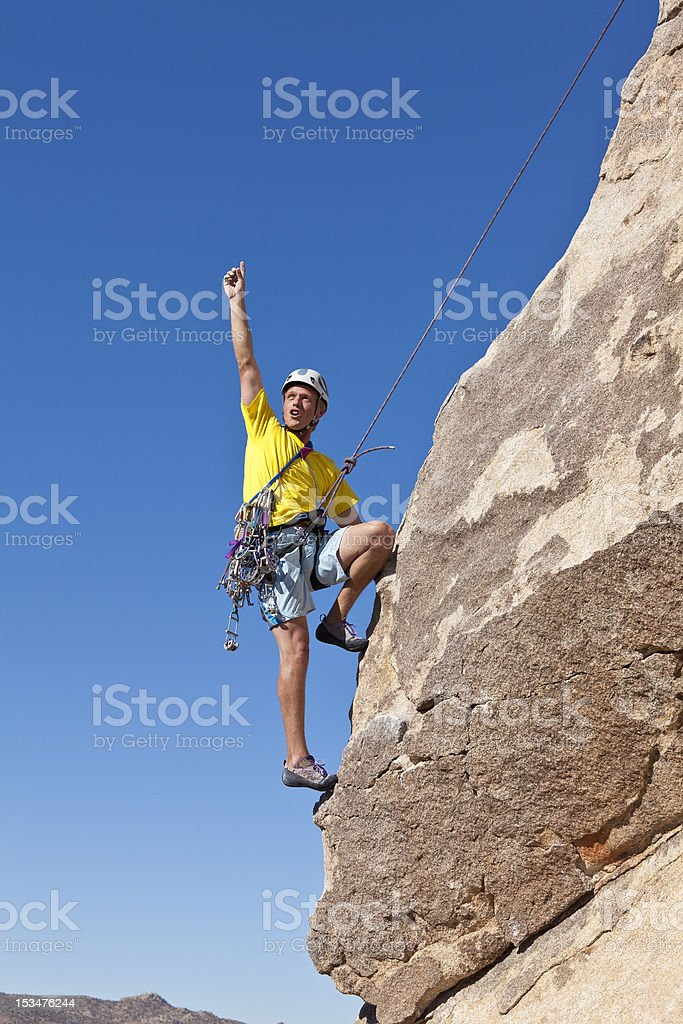 Male rock climber clings to a cliff. royalty-free stock photo