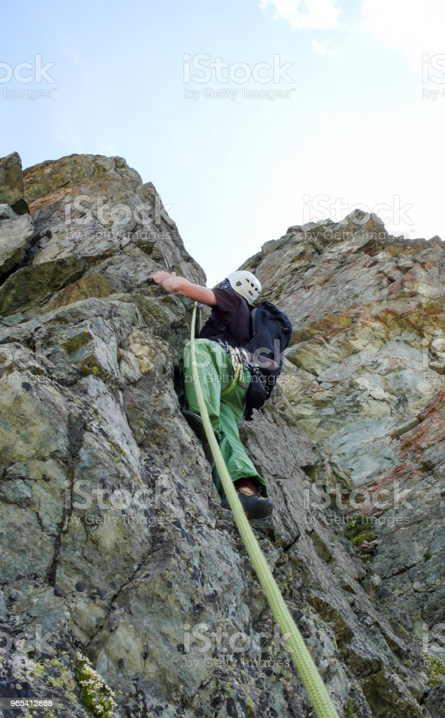 male rock climber on a steep climbing route in the Alps royalty-free stock photo