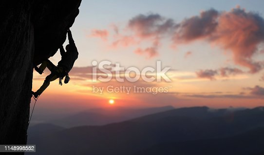 istock Male rock climbing pulling up, doing next step reaching top. Side view. Panoramic mountain view and sunset. Copy space 1148998552