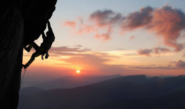 male rock climbing pulling up, doing next step reaching top. side view. panoramic mountain view and sunset. copy space - arrampicata su roccia foto e immagini stock