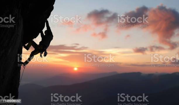 Photo of Male rock climbing pulling up, doing next step reaching top. Side view. Panoramic mountain view and sunset. Copy space
