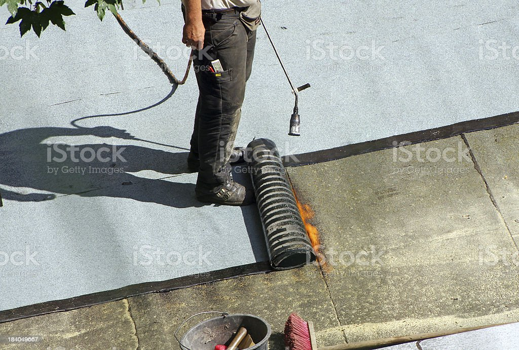 A male roofer at work on top of the roof stock photo