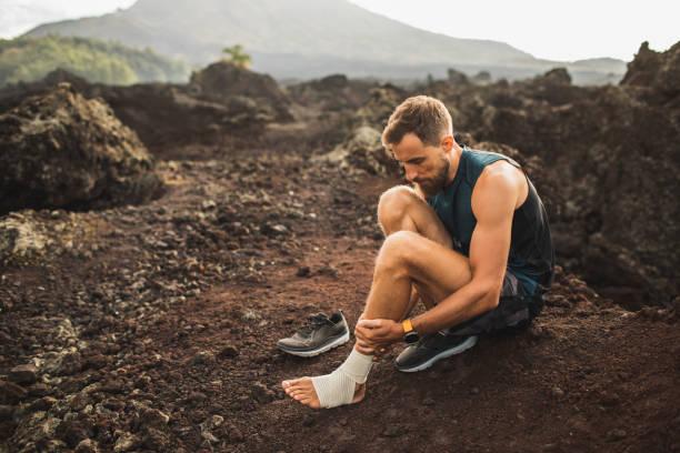 男性ランナーは足首を包帯で包帯。屋外で走っている間に足を負傷。靭帯や腱の捻挫の応急処置。背景に火山の山の眺め。 - 脛 ストックフォトと画像