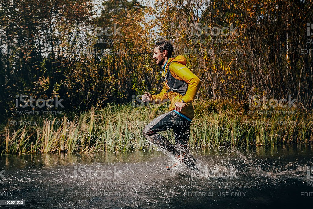 male runner crossing a mountain river, around him water splashes stock photo