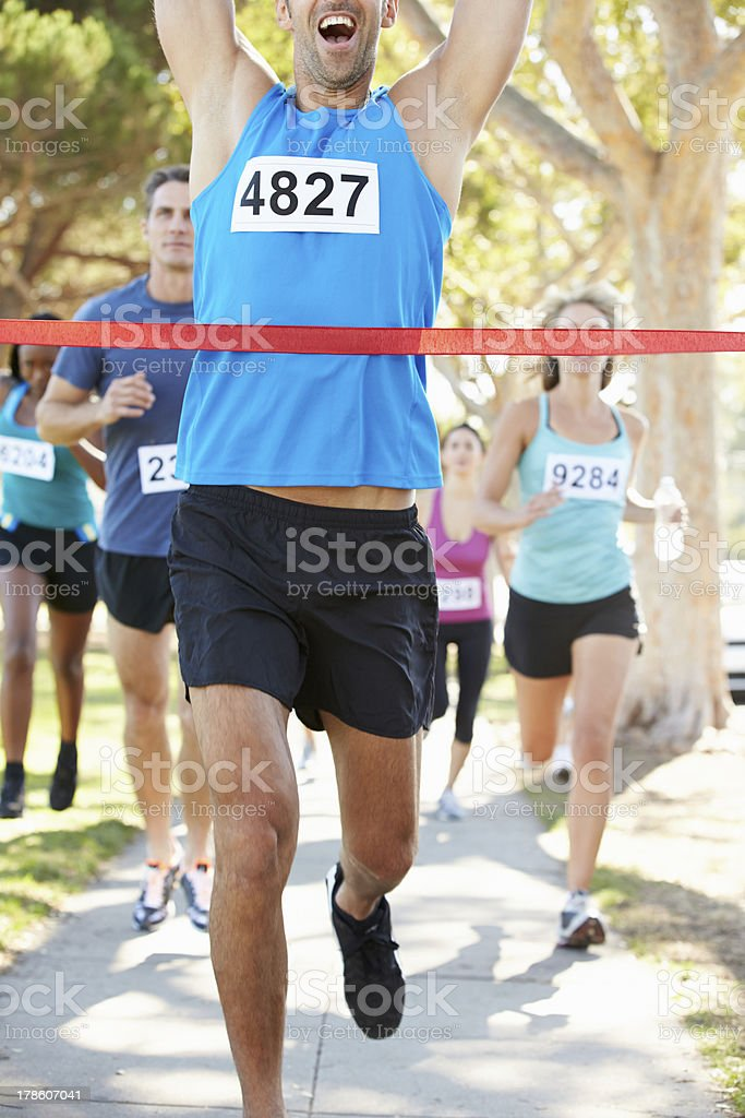 Male runner crossing red tape arms raised winning marathon stock photo