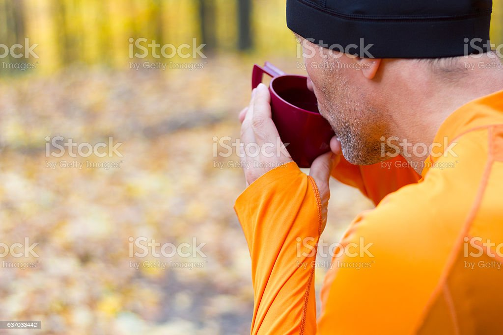 Male runner drining from plastic thermos cup stock photo