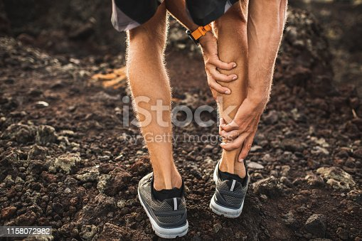 istock Male runner holding injured calf muscle and suffering with pain. Sprain ligament while running outdoors. View from the back close-up. 1158072982