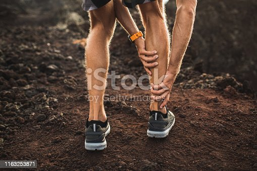 istock Male runner holding injured calf muscle and suffering with pain. Sprain ligament while running outdoors. View from the back close-up. 1163253871
