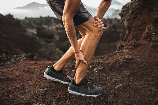istock Male runner holding injured calf muscle and suffering with pain. Sprain ligament while running outdoors. Close-up legs view. 1166298317
