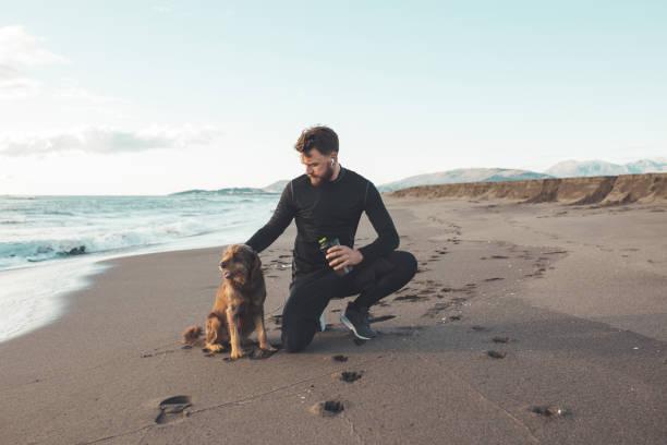 El corredor masculino está descansando después de correr por la mañana con su perro. Está usando el teléfono para una llamada y tomando fotos de sus amigos peludos. - foto de stock
