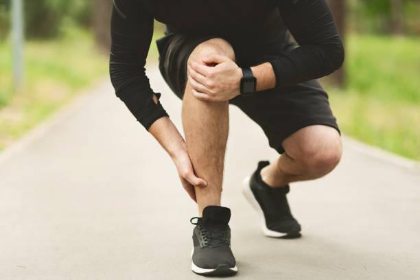 男性ランナーはジョギングで足首の痛みに苦しんでいます - 脛 ストックフォトと画像