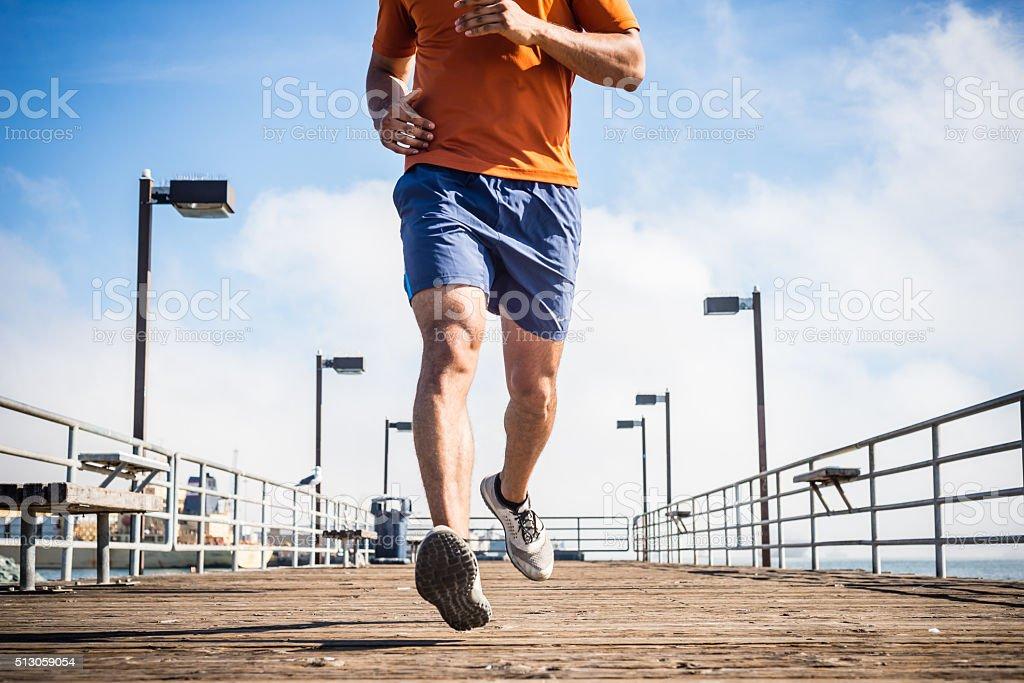 Male Runner Jogging On A Ocean Pier stock photo