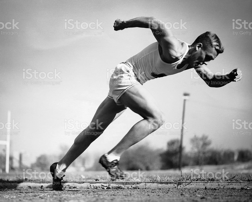 Male runner jumping from starting blocks at beginning of race royalty-free stock photo