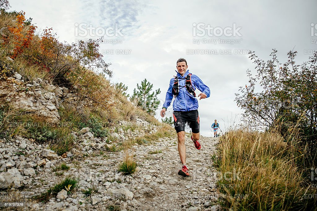 male runner of middle age runs on a mountain trail stock photo