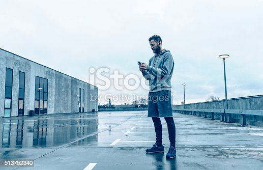 istock Male runner plays with smart phone before run 513752340