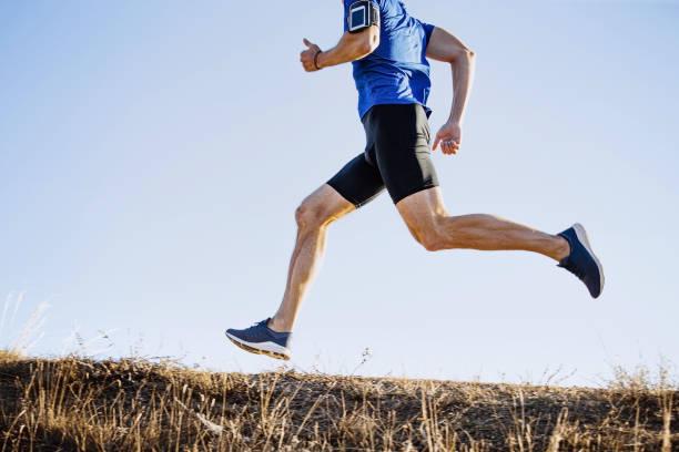 corredor masculino corriendo sendero de montaña - foto de stock