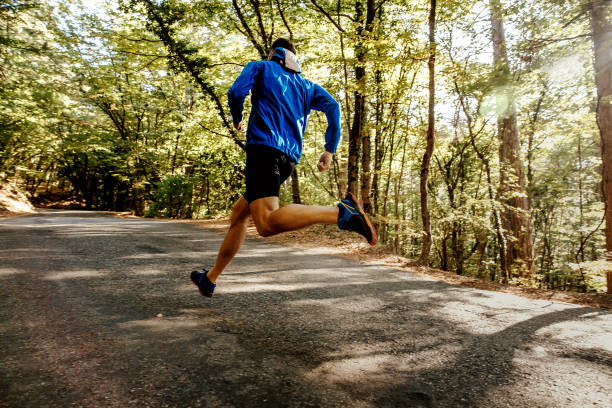 male runner running on forest road stock photo