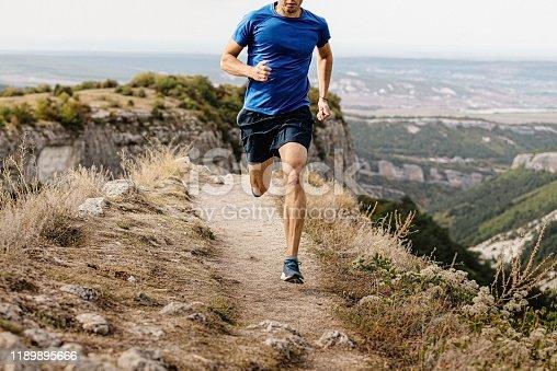 male runner running mountain trail on edge of cliff