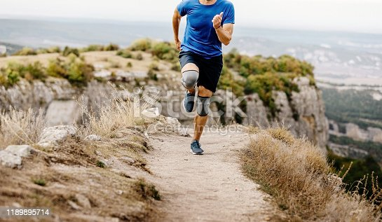male runner running in knee pads on mountain trail