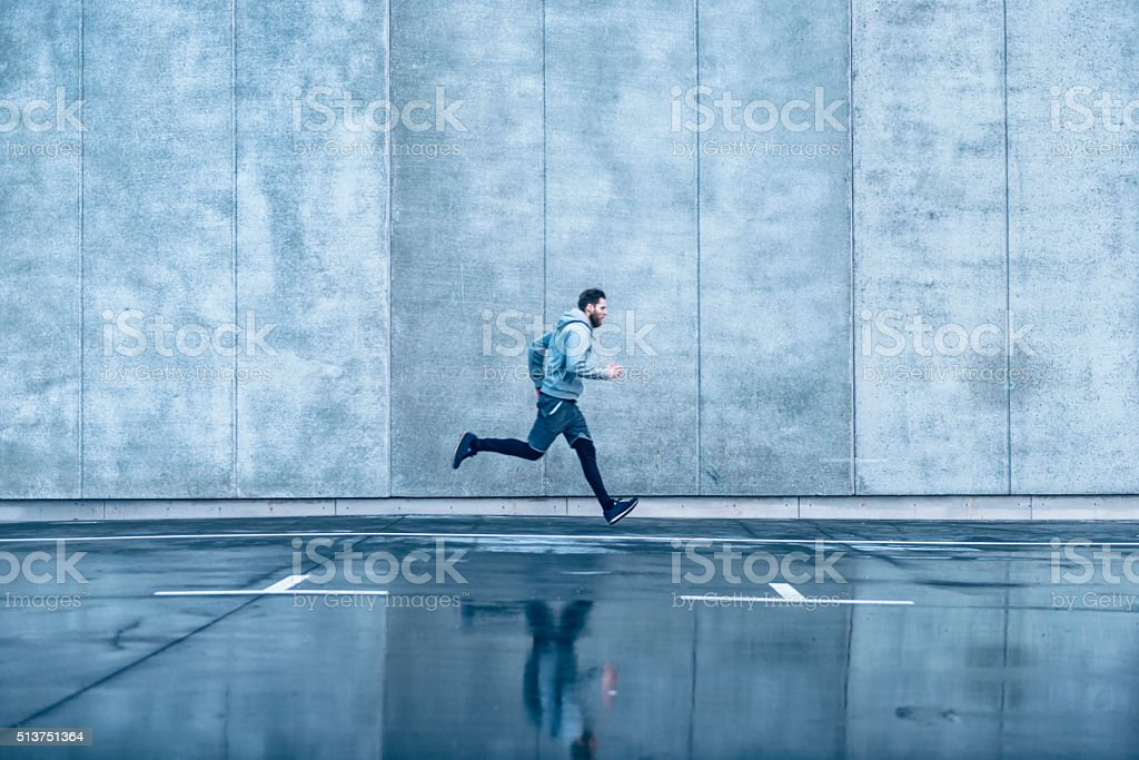 Male runner runs fast in front of concrete building stock photo