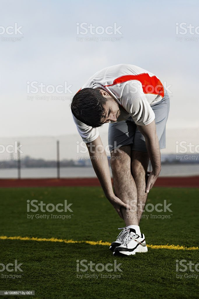 Male runner stretching in park royalty free stockfoto