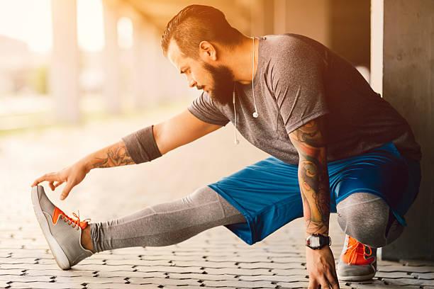 männliche läufer dehnen im schatten. - laufende tattoos stock-fotos und bilder