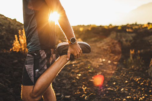 Male runner stretching leg and feet and preparing for running outdoors. Smart watch or fitness tracker on hand. Beautiful sun light on background. Active and healthy lifestyle concept.