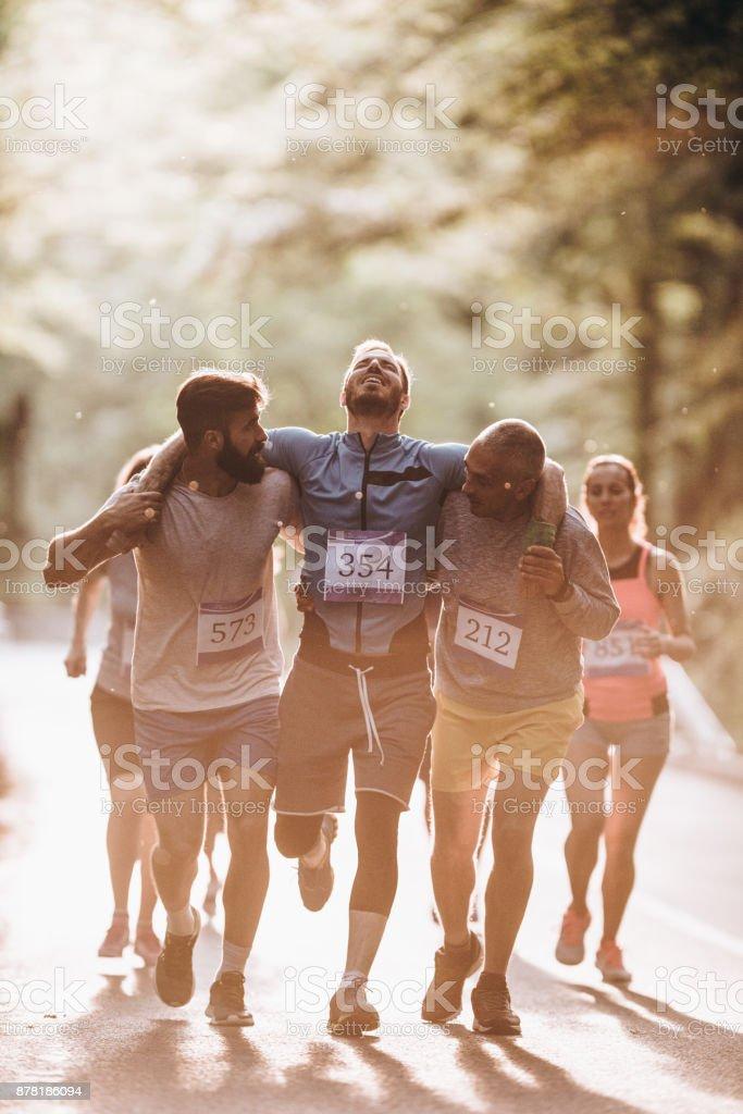 Männliche Läufer tragen verletzte Sportler während der Marathon-Lauf in der Natur. – Foto