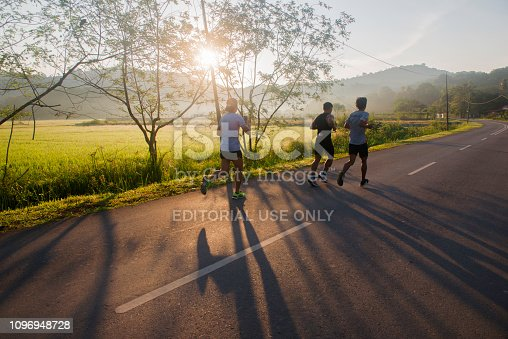 Langkawi, Malaysia - 23 December 2018 : Male runners make their way around the marathon course early in the morning in Chenang, Langkawi.