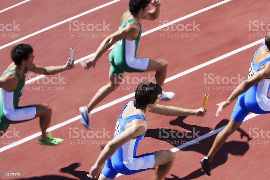 Male runners passing relay baton stock photo