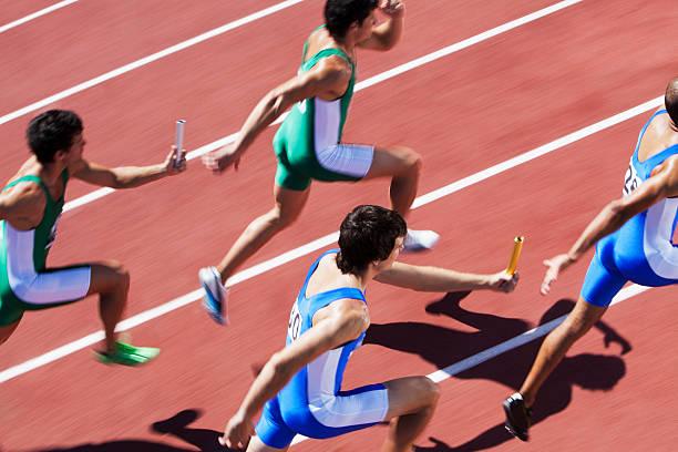 männliche läufer übergeben staffelstab - staffelstab stock-fotos und bilder