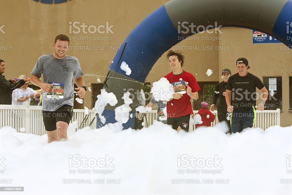 Male Runners Run Through Foam At Finish Line Of Race royalty-free stock photo