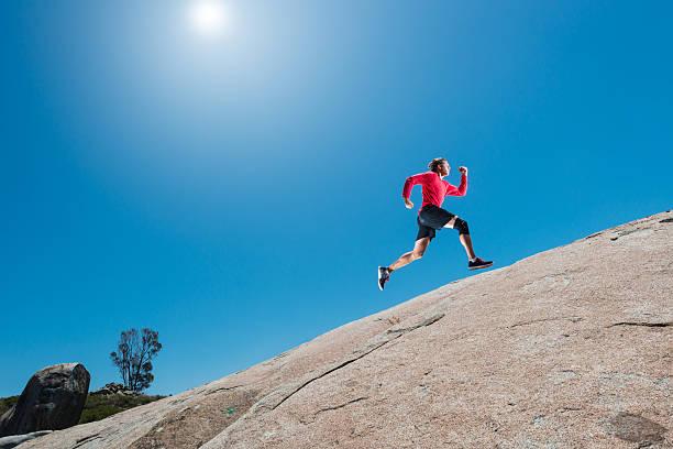 male running up a granite boulder in the mountains - jogging hill bildbanksfoton och bilder
