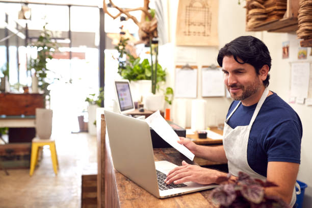Male Sales Assistant Working On Laptop Behind Sales Desk Of Florists Store stock photo