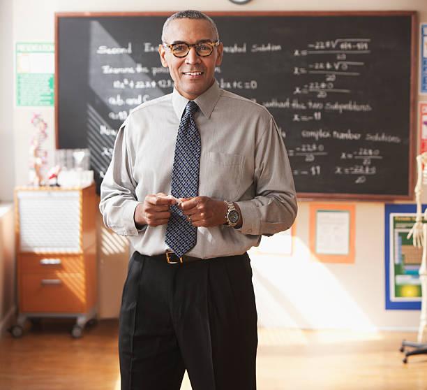 Male school teacher in front of blackboard stock photo