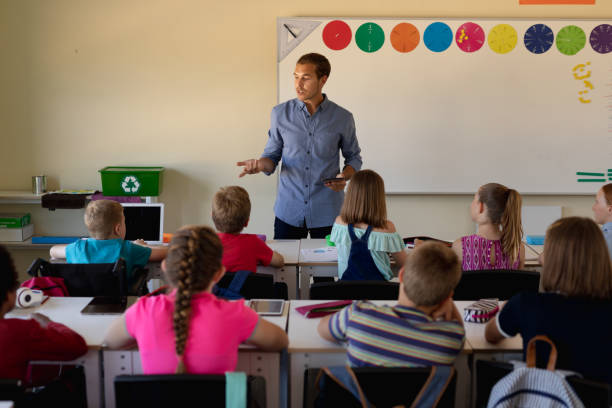 Male school teacher standing in an elementary school classroom with a group of school children stock photo