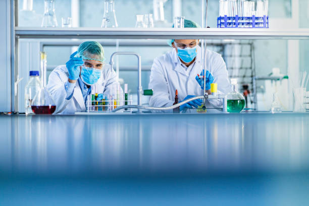 Male scientists working on antiviral drug in laboratory. stock photo
