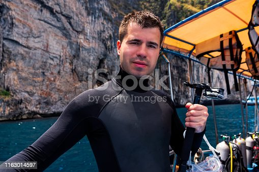 Young Caucasian male scuba diver holding action camera and preparing for diving from boat full of scuba gear, Phi Phi Island, Thailand