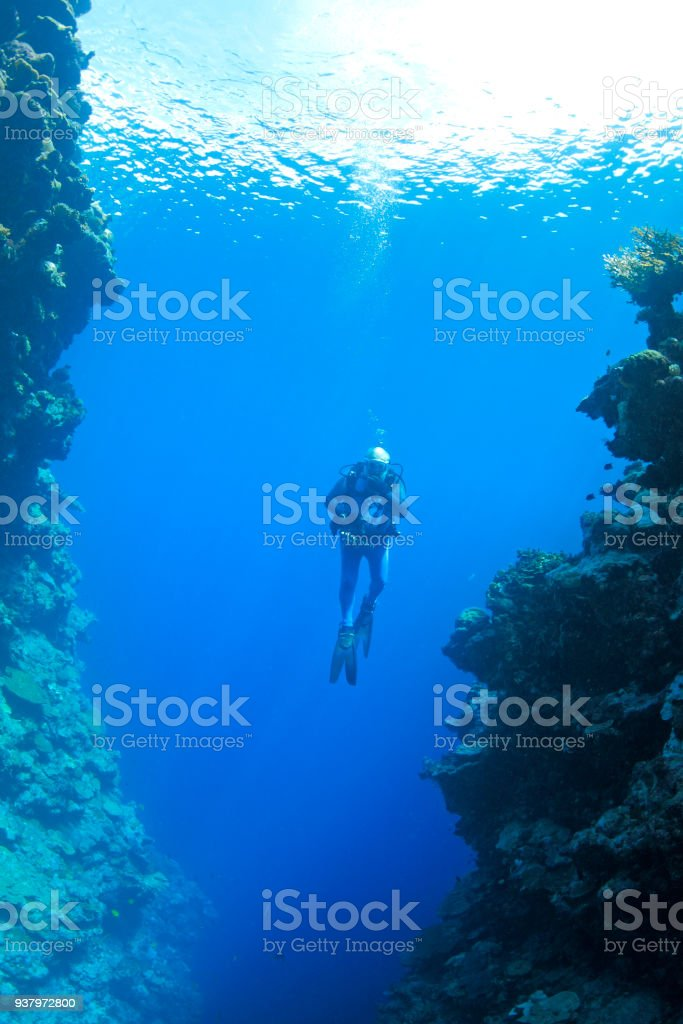 Male Scuba Diver swimming between steep walls underwater stock photo