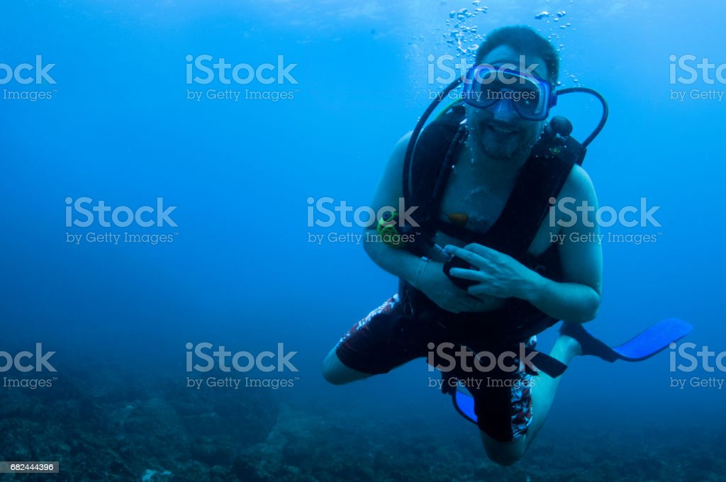 Male scuba diver with regulator out of mouth smiling with blue background in average visiblity royalty-free stock photo