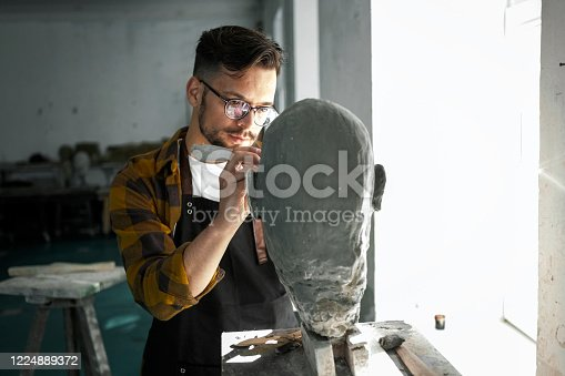 Male Sculptor finishing a clay bust