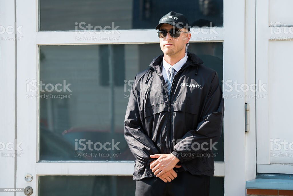 Male Security Guard Standing At The Entrance stock photo
