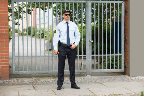 male security guard standing at the entrance - fare la guardia foto e immagini stock