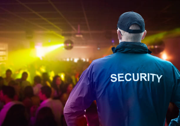 Male Security Officer Standing In Night Club Male Security Officer Wearing Cap Standing In Night Club With His Hands On Hips security staff stock pictures, royalty-free photos & images