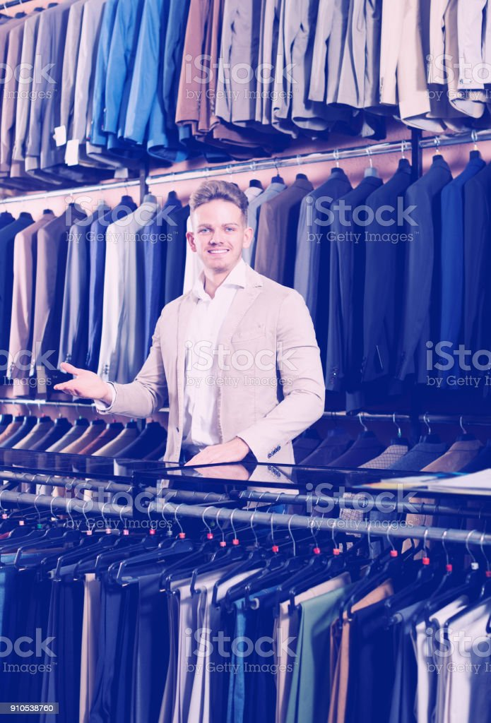 Male seller demonstrating numerous suits stock photo
