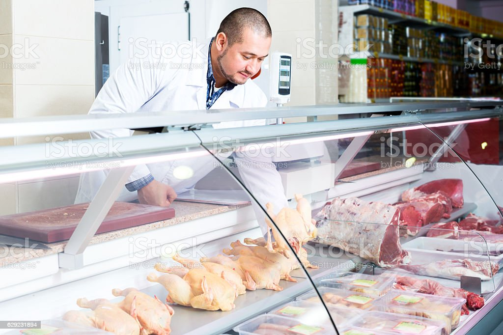 Male seller in halal section at supermarket stock photo